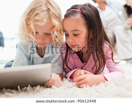 Children using a tablet computer while their parents are in the background in a living room - stock photo