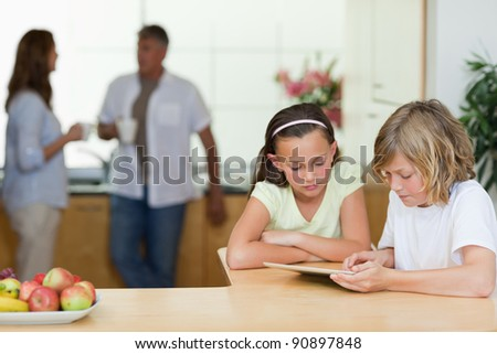 Children using tablet in the kitchen with their parents behind them - stock photo