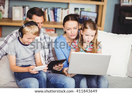 Children using technologies with parents on sofa at home