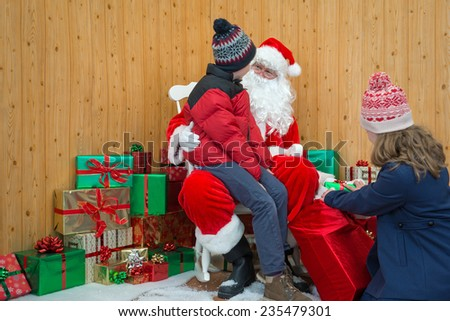 Children visiting Santa in his Christmas grotto - stock photo