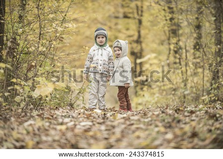 Children  walking and playing in a forest with yellow leaves - stock photo