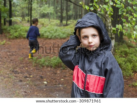 Children walking and playing in forest after the rain - stock photo