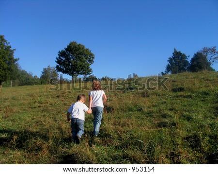 Children walking up a hill - stock photo