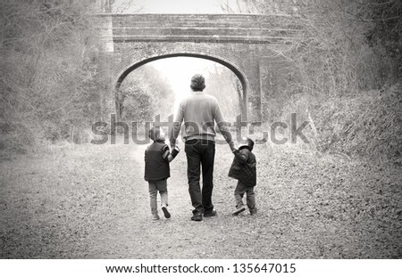 children walking with their father - stock photo