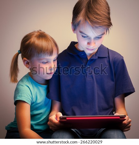 Children wearing casual clothes playing or watching a movie on a touch pad at home. Boy and girl are half-siblings. Brother is holding tablet with red cover. - stock photo