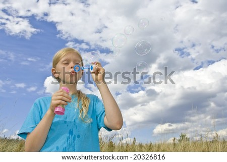 Children wearing colorful T-shirts blowing bubbles on summer meadow