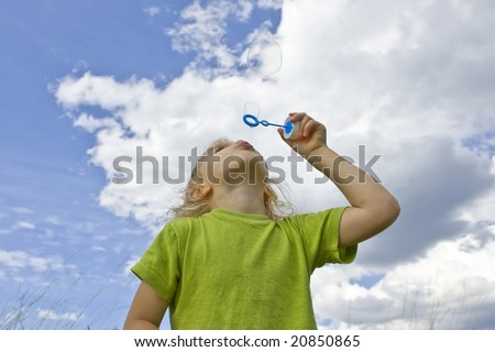 Children wearing colorful T-shirts blowing bubbles on summer meadow - stock photo