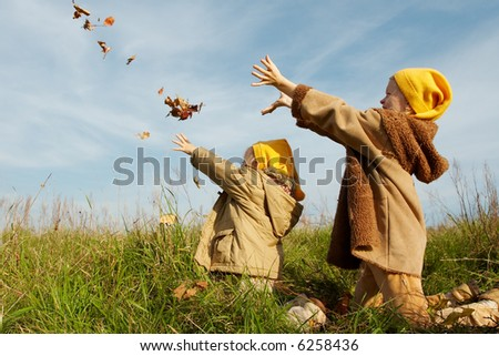 Children wearing yellow caps  playing on autumnal meadow - stock photo
