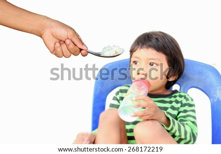 Children who are tired of rice,but he want some milk,focus at rice. - stock photo