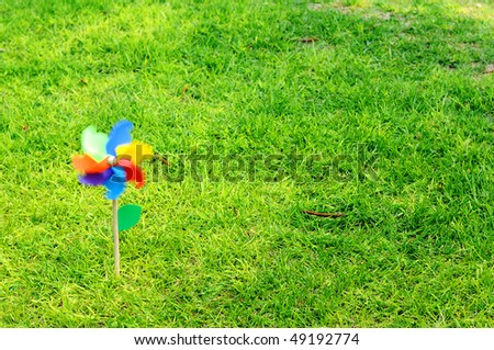 Children windmill on a sunny green lawn