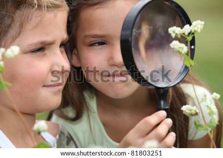 Children with a magnifying glass - stock photo