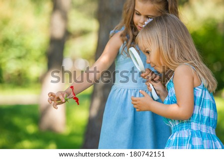 Children with a magnifying glass. Two little sisters of friends looking through magnifier at flower - stock photo