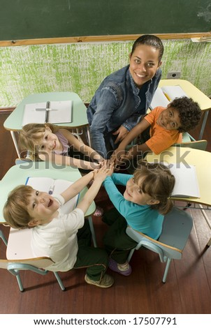 Children with a teacher in a classroom.  Their hands are clasped as a group.  They are facing the camera and are smiling. Vertically framed shot. - stock photo