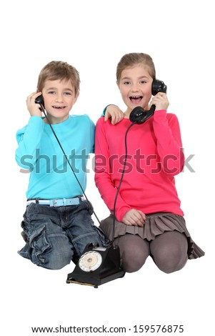 Children with an antique phone - stock photo