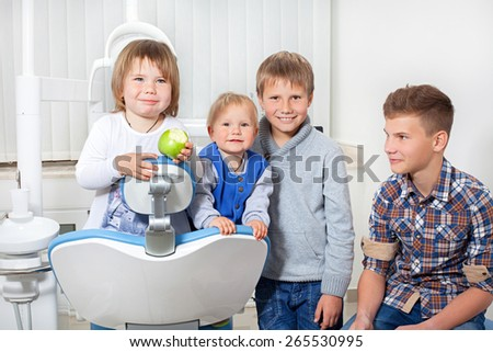 children with apple in the dental office smiling and looking at camera - stock photo