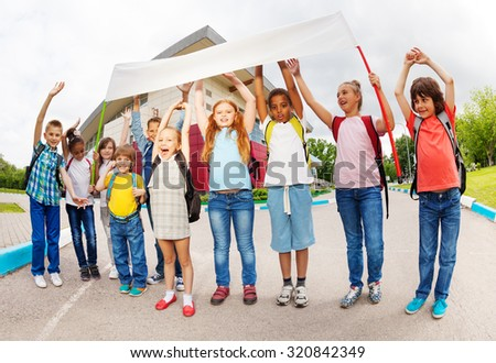 Children with arms up holding placard standing - stock photo