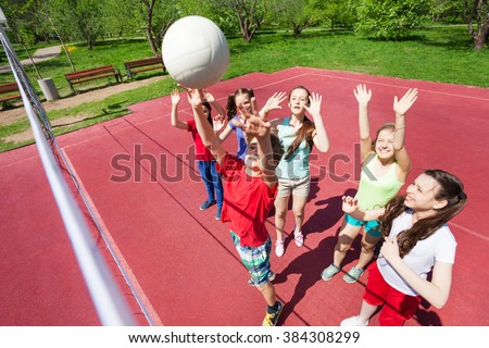 Children with arms up to ball play volleyball near the net on the court during sunny summer day outside - stock photo