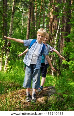 Children with backpacks walking in a summer forest, go hiking and having fun outdoor