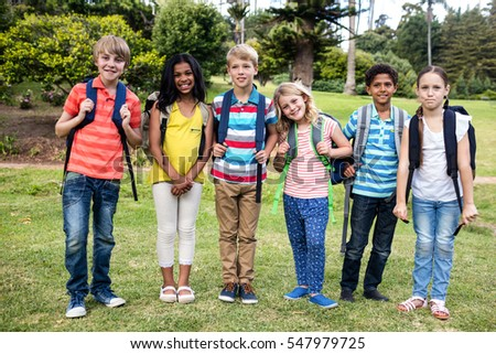 Children with bags standing together in park