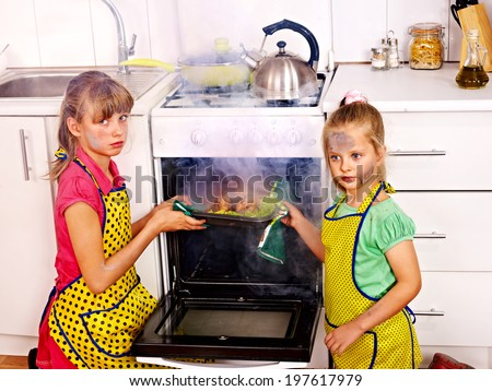 Children with  burned chicken cooking at kitchen. - stock photo