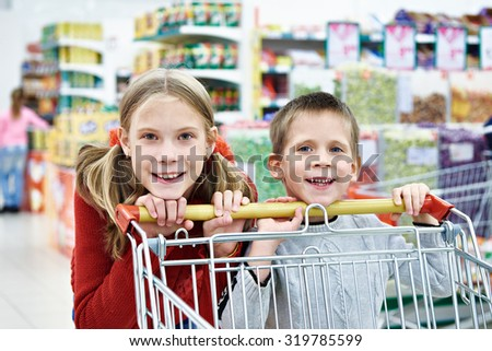 Children with cart shopping in supermarket
