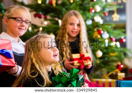 Children with Christmas gift on Christmas day in family home under tree - stock photo