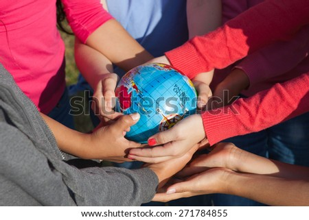 Children with colorful shirts hold a globe  - stock photo