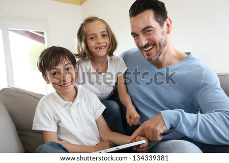Children with daddy at home using digital tablet - stock photo
