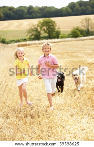 Children With Dogs Running Through Summer Harvested Field - stock photo