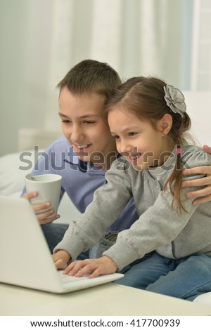 Children with laptop at home