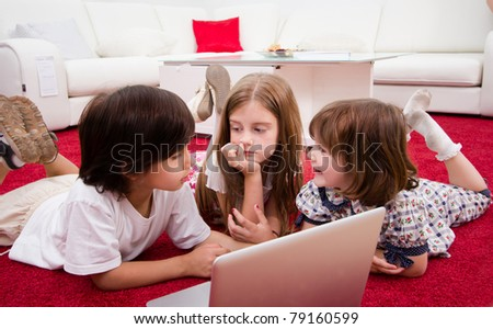 Children with laptop laying on floor - stock photo