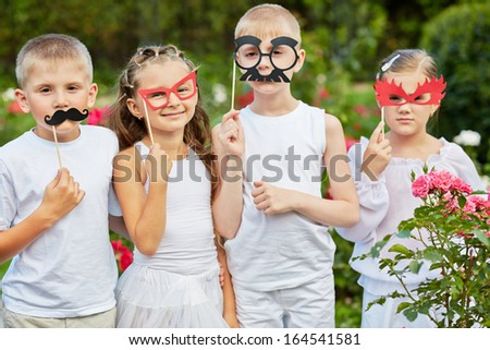 Children with masks on stiks stand together in summer park - stock photo