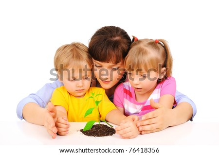 Children with mom protecting a plant - stock photo