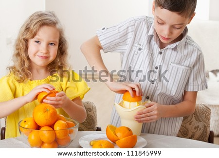 Children with oranges. Happy little girl and boy squeezed fresh juice.