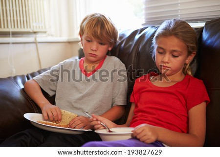 Children With Poor Diet Eating Meal On Sofa At Home - stock photo