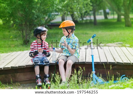 children with rollers and scooter sit on a wooden platform in the park - stock photo