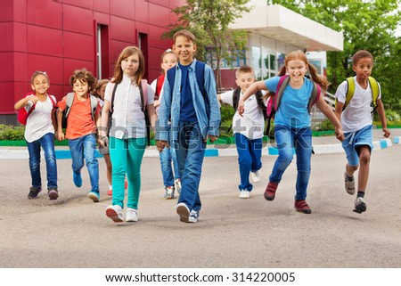 Children with rucksacks near school walking - stock photo