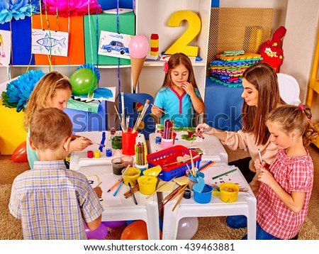 Children with school teacher woman painting on paper at table in primary painting school . - stock photo