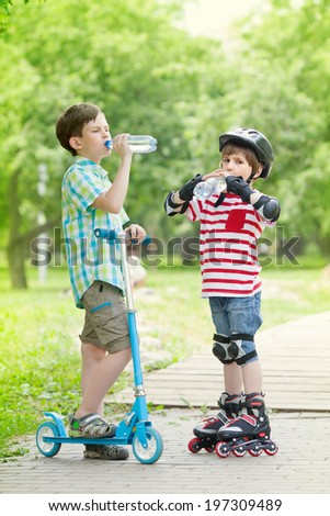 children with scooter and rollers drink water, standing on the path in the Park - stock photo