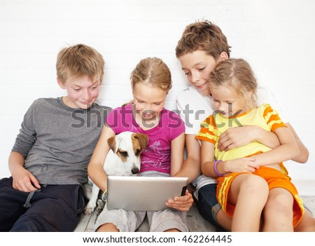 Children with tablet. Group kids playing
