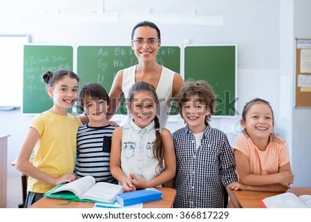 Children with teacher at school - stock photo
