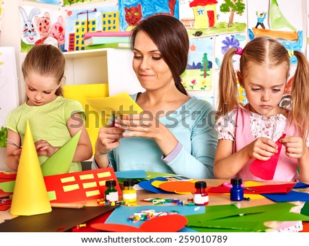 Children  with teacher cutting out scissors paper in preschool. - stock photo