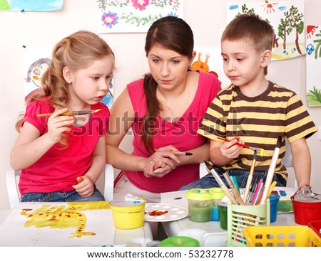 Children with teacher painting  paints in play room. Child care. - stock photo