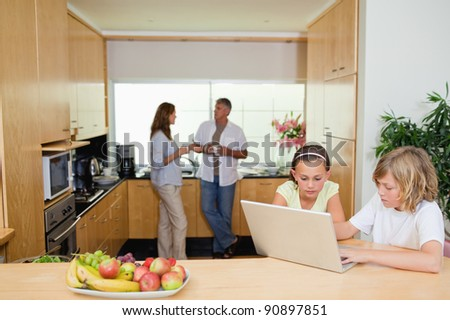 Children with their laptop in the kitchen and parents behind them - stock photo