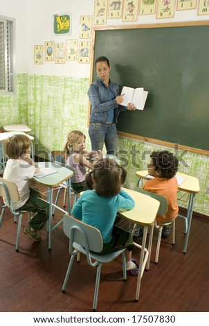 Children with their teacher in a classroom.  She is holding a book in front of the class. Vertically framed shot. - stock photo