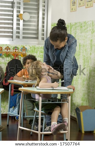 Children with their teacher in a classroom.  They are smiling. Vertically framed shot. - stock photo