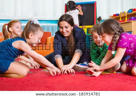 Children with tutor playing development games at kindergarten