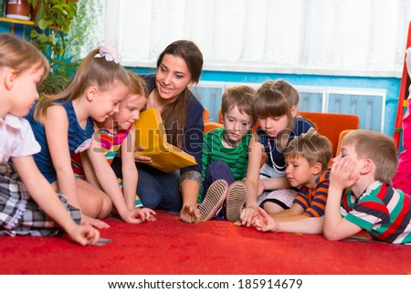Children with tutor reading book at kindergarten