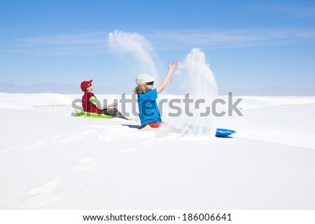 Children wizards: call sandy spirit. Children thrown in the air white sand.  White Sands, New Mexico, USA - stock photo