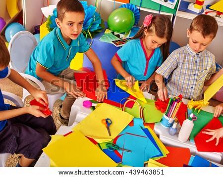 Children working with colored paper on table in kindergarten .Creative development of children. - stock photo